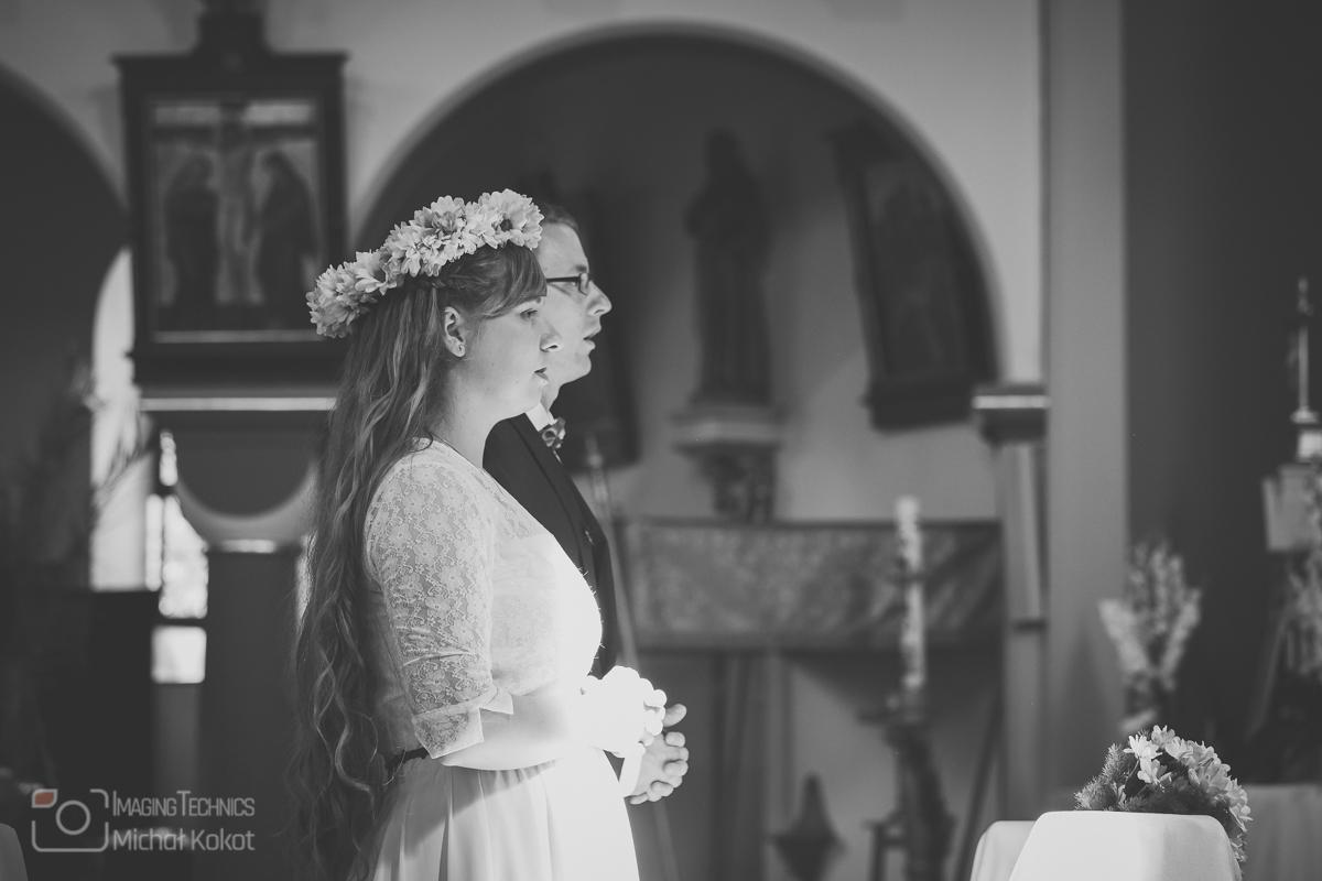Para młoda w skupieniu podczas ślubu